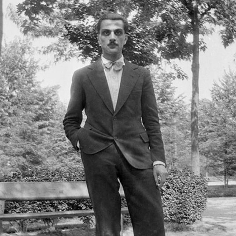 Portrait of Italian designer and artist Carlo Mollino standing up wearing a suit and with a cigarette on his hand