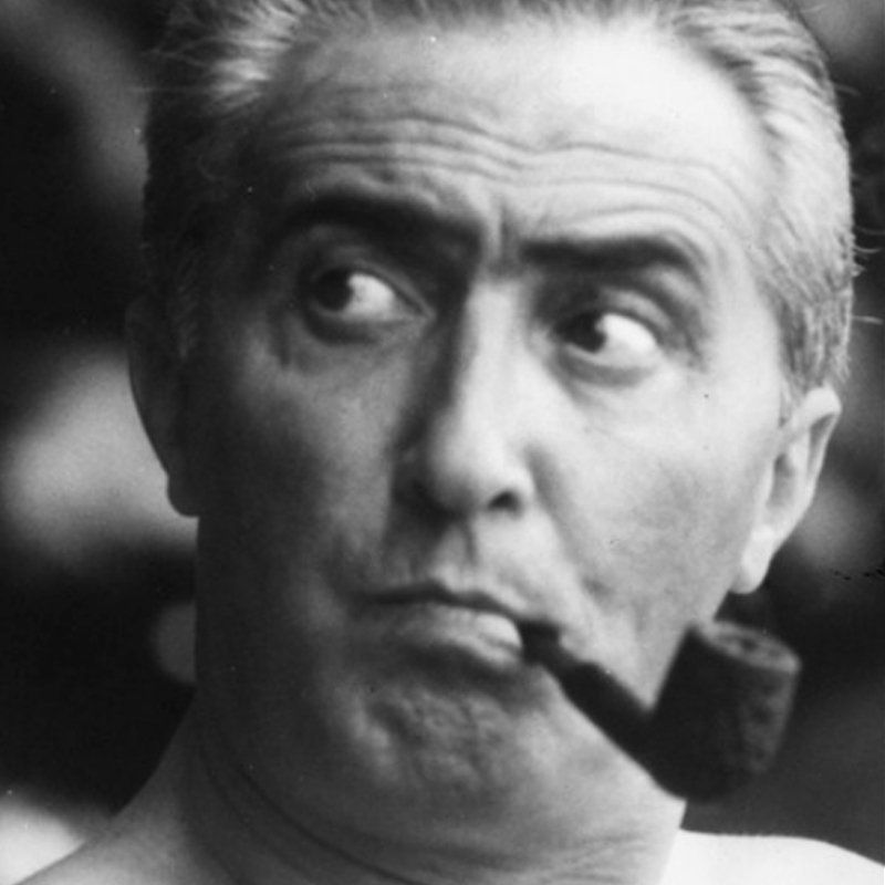 Portrait of Italian light designer and founder of Arteluce Gino Sarfatti smoking a pipe looking away from the camera