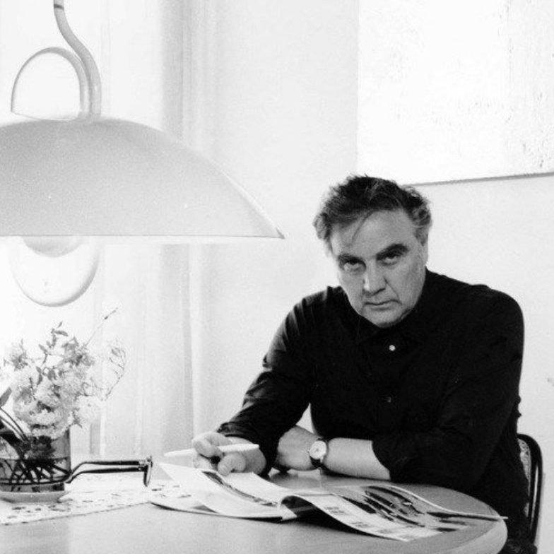 Portrait of Italian lighting designer Elio Martinelli wearing a black shirt and reading a magazine