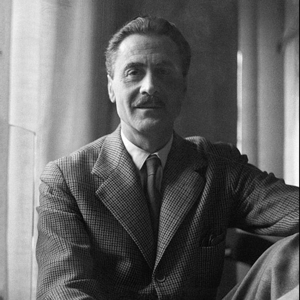 Portrait of Italian architect and designer Franco Albini seating with a leg up and looking at the camera at Italian design and furniture gallery Casati Gallery