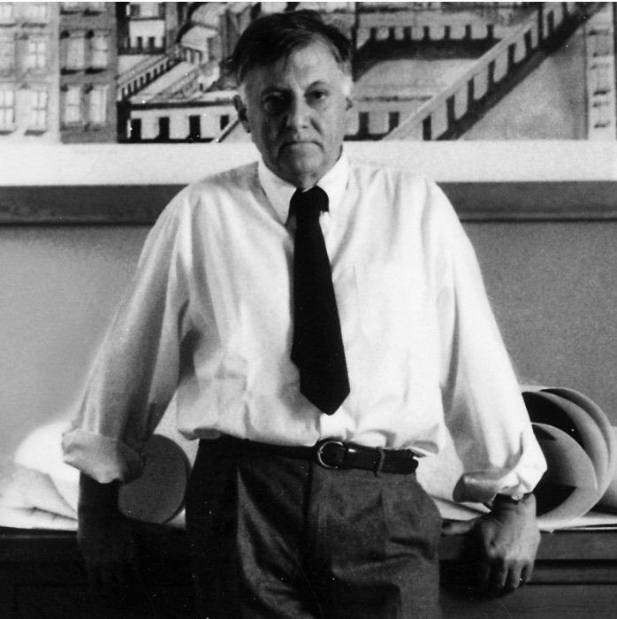Portrait of Italian architect Aldo Rossi in front of his desk with one of his architectural drawing on the background