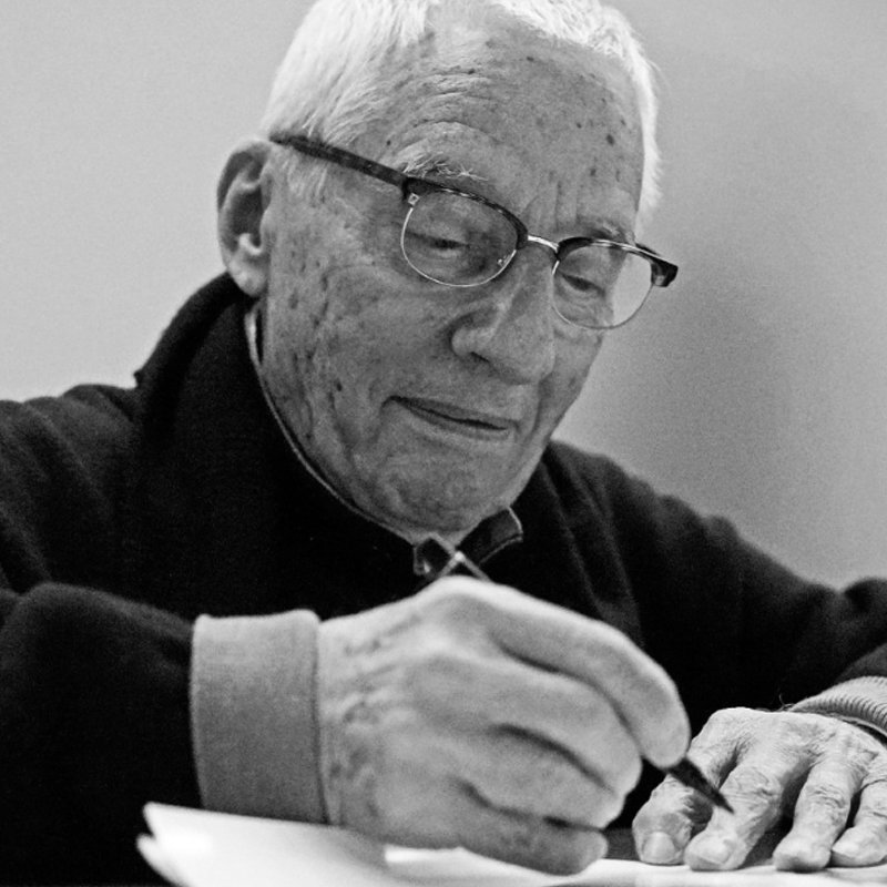 Italian architect and designer Alessandro Mendini writing a document on his desk wearing a black shirt