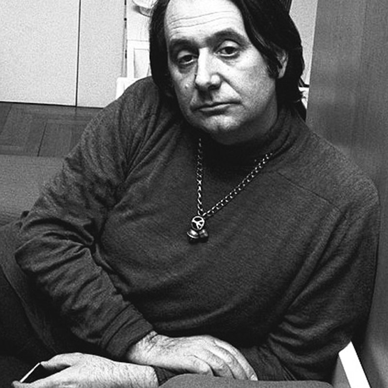 Portrait of Ettore Sottsass from 1969 leaning on his side with a turtle neck