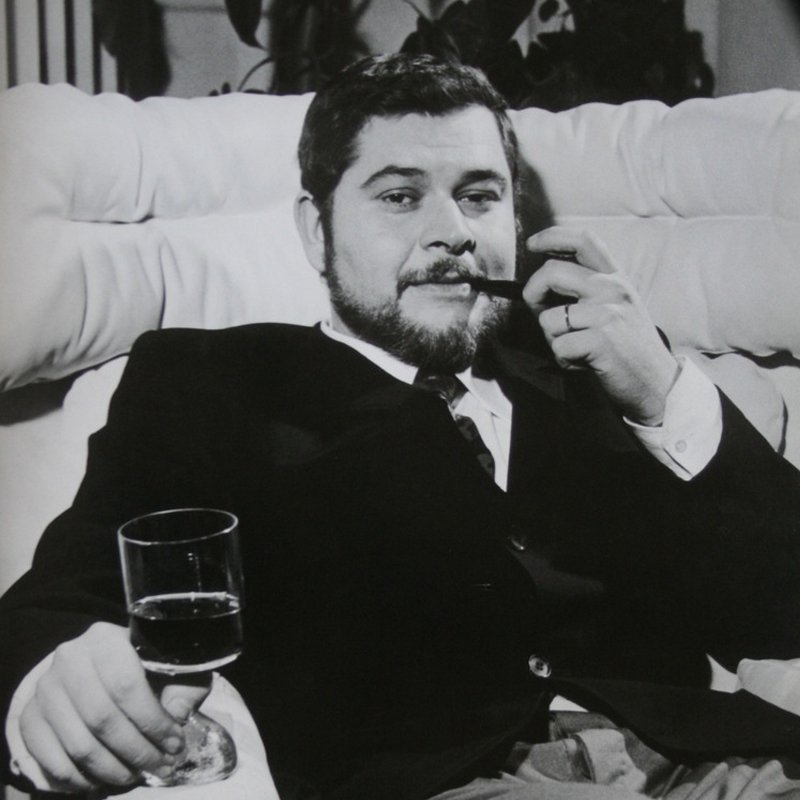 Portrait of Italian designer and architect Joe Colombo seating on a white Elda chair with a pipe on one hand and a drink on the other