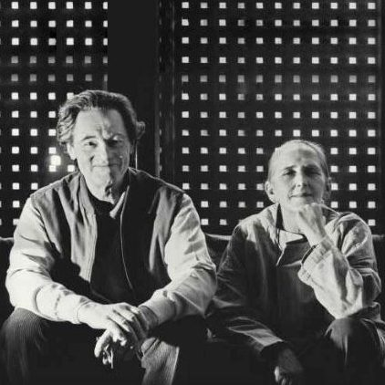 Portrait of Italian architects and designers Afra and Tobia Scarpa seating down withe their arms on their legs and smilling