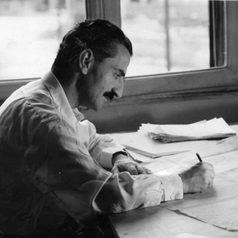 Profile portrait of Italian architect and designer Carlo de Carli seating on his desk writing on a piece of paper