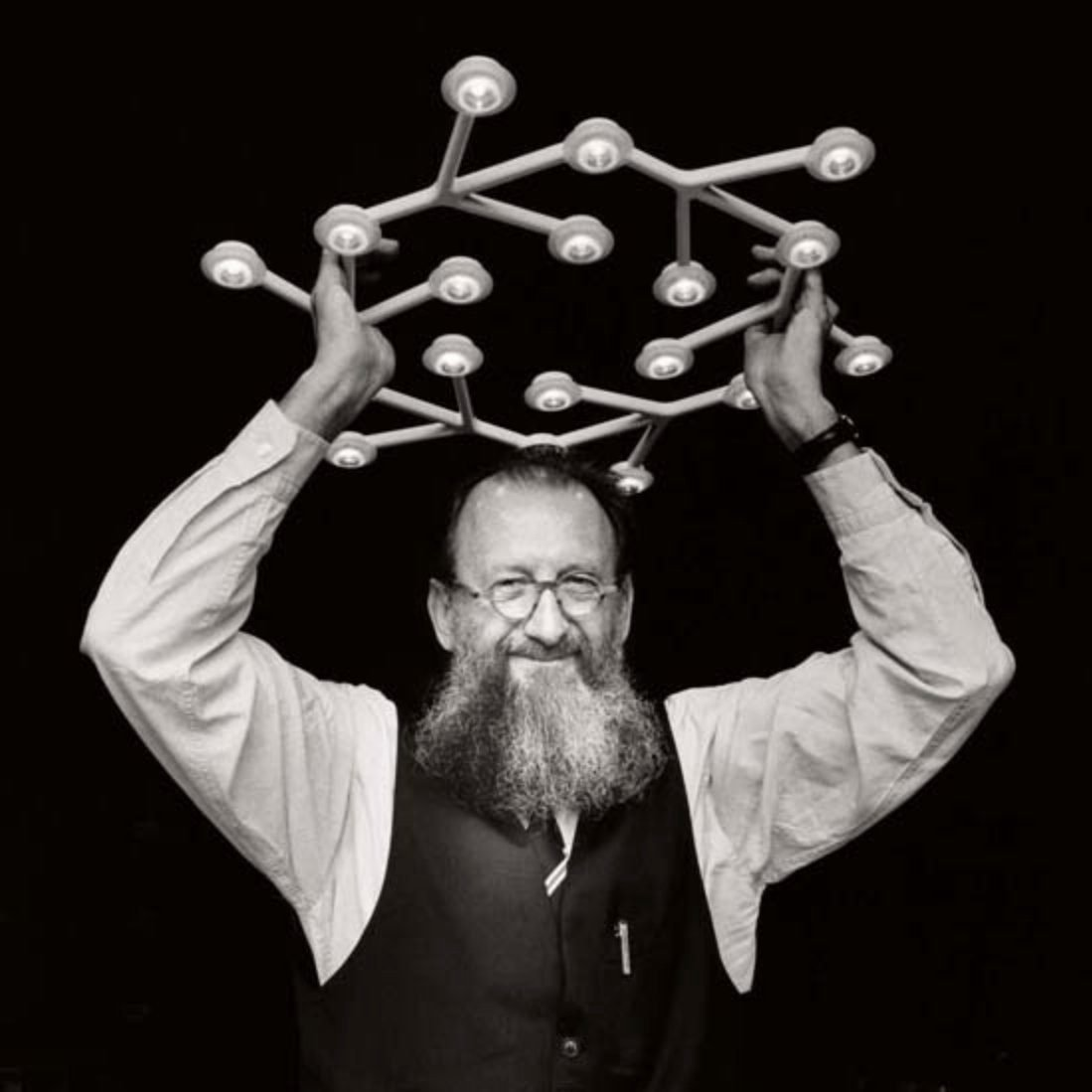 Italian designer Michele de Luchi with a long beard holding his Led Net lamp manufactured by Artemide