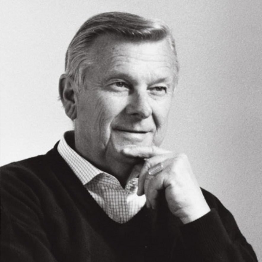 Portrait of Italian designer and architect Tito Agnoli with his hand on is face and wearing a sweater