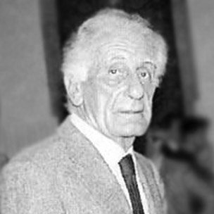 Portrait of Italian designer Gianfranco Frattini with a suit and black tie looking at the camera