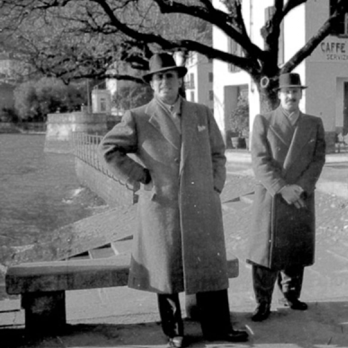 Photograph of architects Mario Asnago and Claudio Vender wearing coats outside and looking at the camera