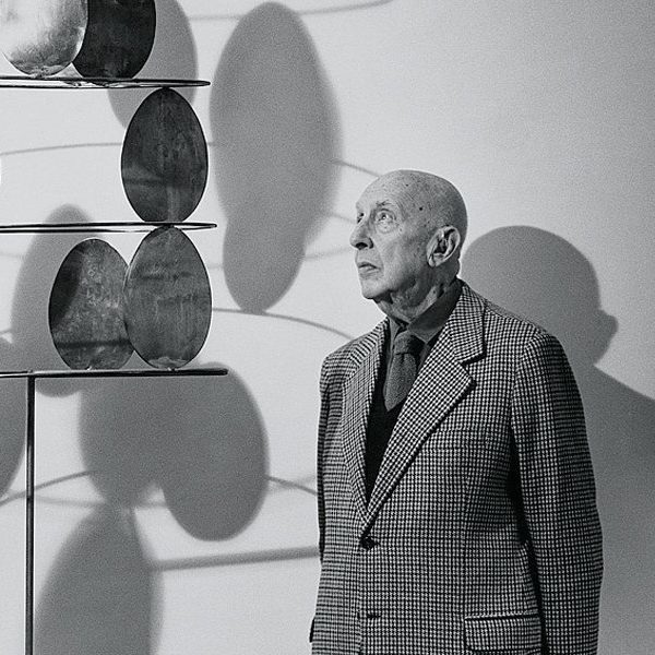 Portrait of Italian artist Fausto Melotti in front of one of his sculptures