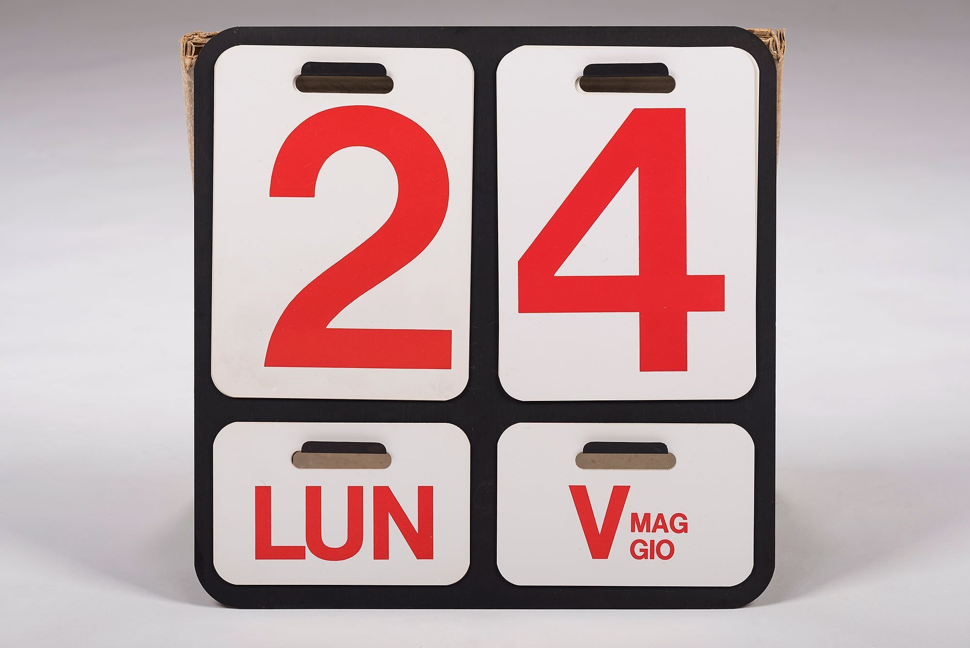 Wall calendar - comprised of anodized aluminum back plate and white PVC-sheets with numbers and month and day abbreviation printed in red.