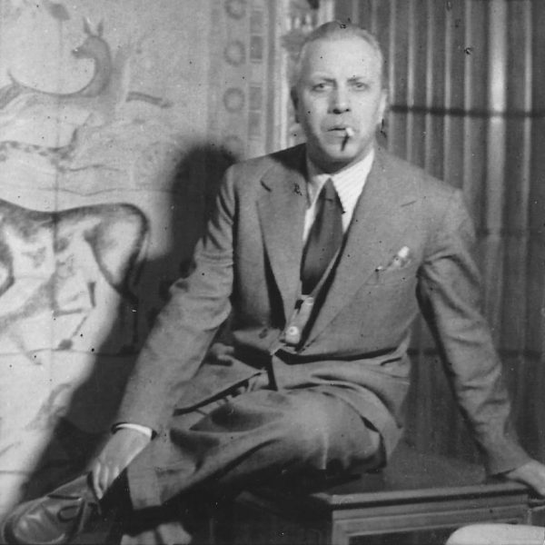Portrait of Italian designer Paolo Buffa sitting on a table and with a cigarette in his mouth