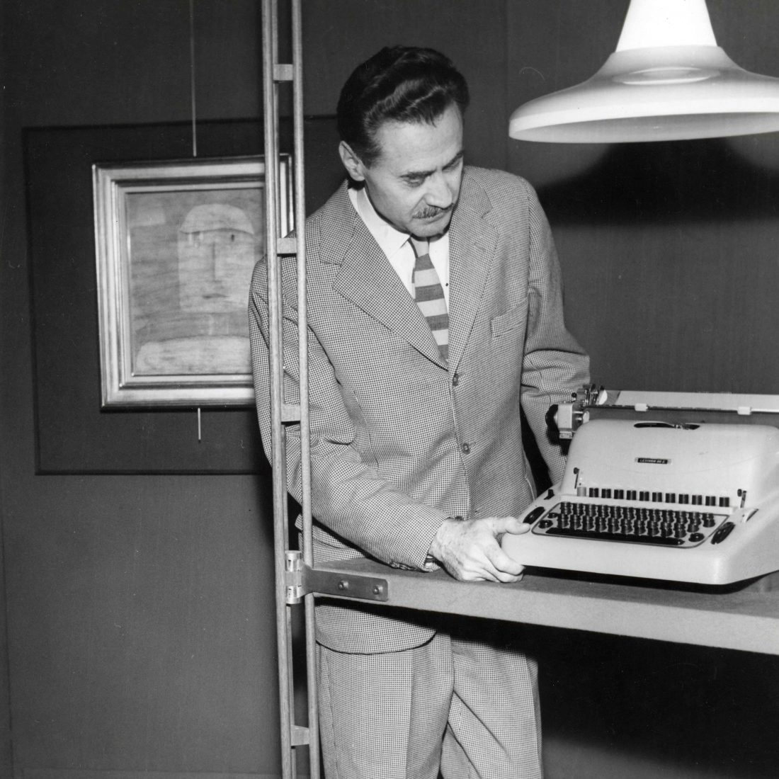 Franco Albini looking at at typewriter