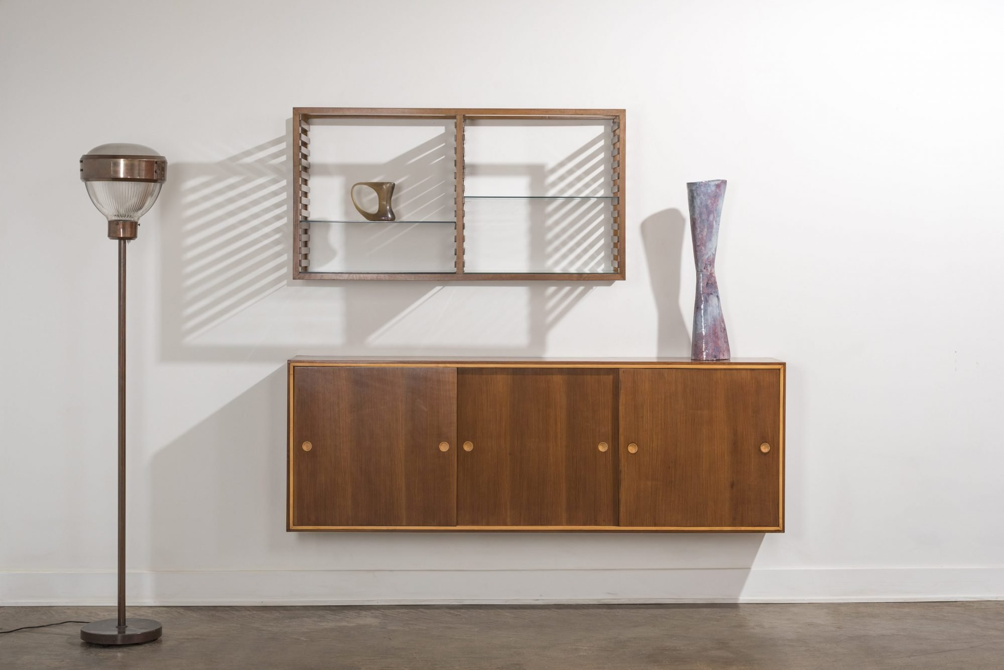 Front view with lateral shade of Franco Albini bookshelf and wall-mounted cabinet a ceramic Melotti vase, a Ferro murano vase, and a BBPR floor lamp at Italian design and furniture Casati Gallery